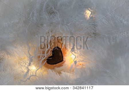Brown Heart In The Folds Of Light Fleecy Fabric. A Plush Heart Illuminated By Light Bulbs In A Fabri