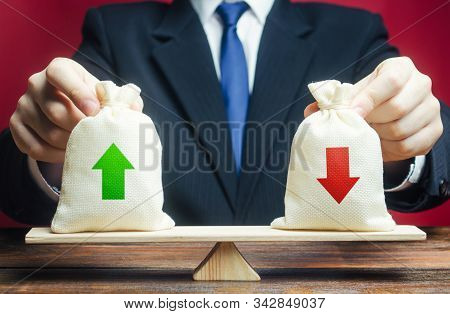 The Businessman Holds On Scales Bags Profits Expenses. Summary And Balance Sheet. Income And Costs.