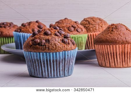 A Few Chocolate-sprinkled Muffins In Colored Cups On A White Wooden Surface. In The Background, Muff