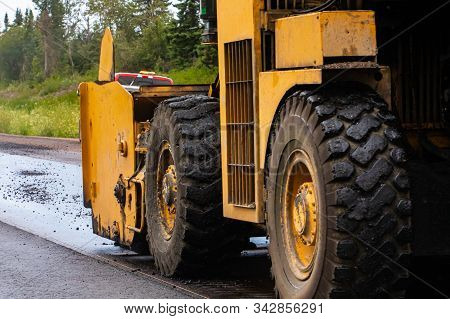 A Close Up Shot On The Large Wheels And Tires Of An Industrial Heavy Plant Yellow Machine Used Durin