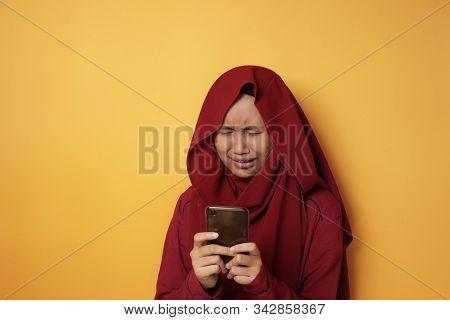 Portrait Of Cute Beautiful Asian Muslim Teenage Girl Wearing Hijab Crying Sad When Receiving Bad New