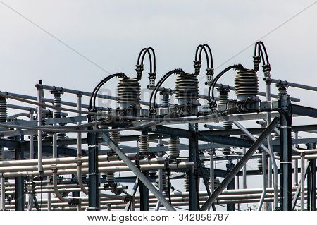 High Voltage Electrical Substation Tower Top, Close Up On A Closed Electrical Isolator Or Electrical