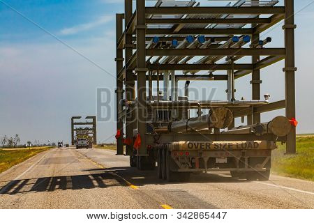 Oversize Loaded Truck Traveling Along Road On A Sunny Day. Detail Of Metal Tubes Beign Transported.