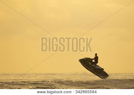 Silhouette Of Man Riding A Water Motor Bike And Jumping Over A Wave On Sunrise
