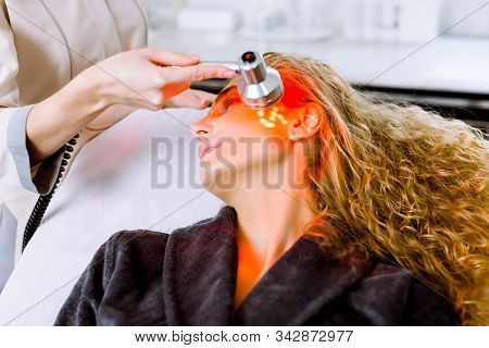 Beautician Doing Red Led Light Therapy To Blond Woman In Beauty Salon, Facial Photo Therapy For Skin