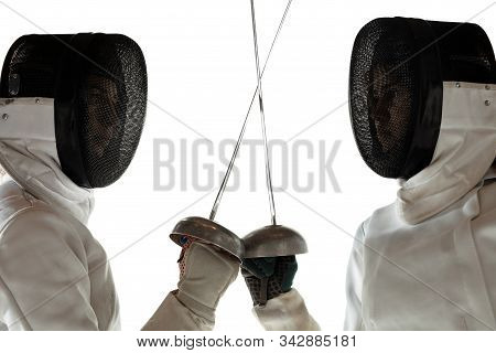 Standoff. Close Up Of Teen Girls In Fencing Costumes With Swords In Hands On White Background. Young