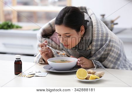 Sick Young Woman Eating Soup To Cure Flu At Table In Kitchen