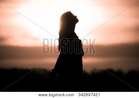 Youth Woman Soul At White Sun Meditation Dreaming Past Times. Silhouette In Front Of Sunset Or Sunri