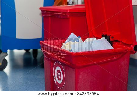 Biological Risk Waste Disposed Of In The Red Trash Bag At A Operating Room In A Hospital. Sign Showi