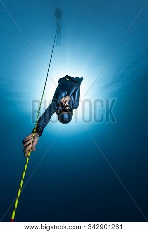 Freediver descends along the rope into the depth while another freediver relaxes on the buoy