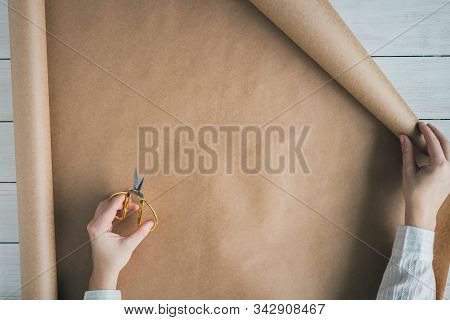 Female Hands Unfolding A Roll Of Wrapping Brown Craft Paper For Packing Gifts And Flowers On The Woo
