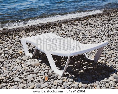 Chaise Lounge Is White On A Stony Beach By The Coastline. Chaise Lounge By The Sea.