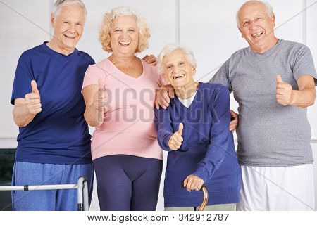 Laughing group of seniors in retirement home holding their thumbs up