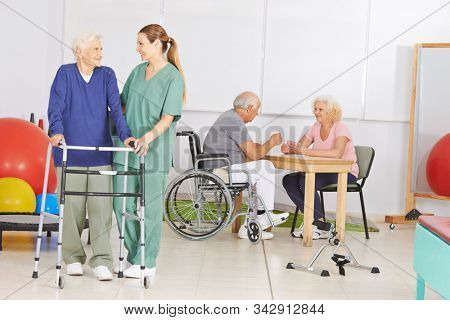 Seniors with a nurse in a nursing home during physiotherapy