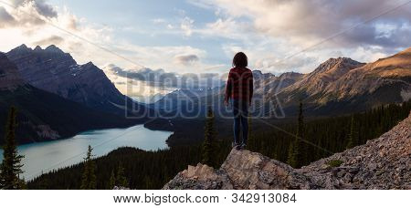 Adventurous Girl With Open Arms Standing On The Edge Of A Cliff Overlooking The Beautiful Canadian R