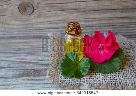 Geranium Essential Oil In A Glass Bottle With Flower And Leaf Of The Geranium Plant On Wooden Backgr