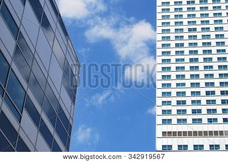 Geometric Reflection: Partly Cloudy Sky Reflected By Window Panes Of Office Building. Surface Of Gla