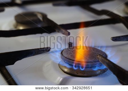 Flames From Burning Gas On A Stove. Among The Blue Flame, One Red Stands Out Brightly. Cooking In Th