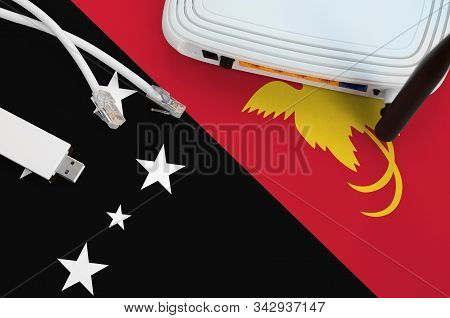 Papua New Guinea Flag Depicted On Table With Internet Rj45 Cable, Wireless Usb Wifi Adapter And Rout