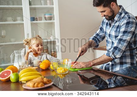 Smiling Little Girl Watching How Father Cutting Grapefruit