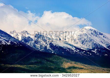High Tatras Mountain Ridge In Springtime. Snow Capped Rocky Peaks In Dramatic Dappled Sunlight Benea