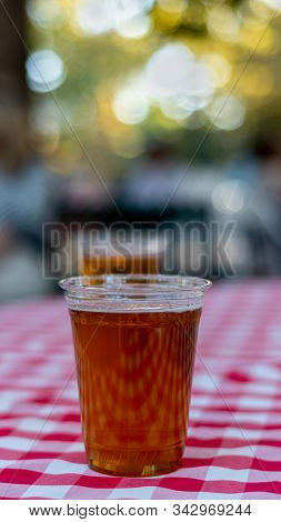 Ipa Beer In A Plastic Cup Outoors Over A Chess-pattern Tablecloth. Summer Cooling Concept