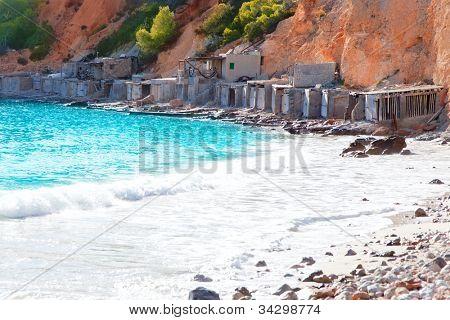 Cala d Hort Ibiza beach with traditional wood boat mooring in Balearic island