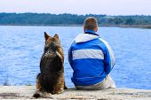 man and dog sitting on a sea berth poster