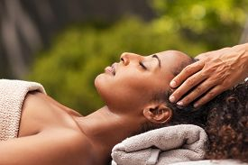 Beautiful black woman getting face massage in luxury spa. African american girl relaxing in resort spa while getting head massage. Masseuse hands massaging black woman with closed eyes at resort spa.