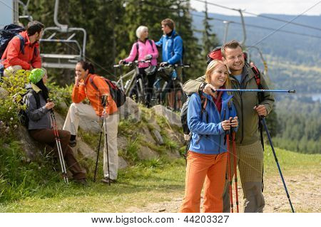 Young hikers and cyclists talking and watching landscape