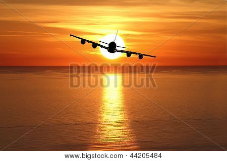 Beautiful sunset with airplane over the sea