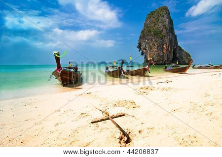 Tropical Beach Landscape. Thai Traditional Long Tail Boats At Ocean Gulf Under Blue Sky. Thailand