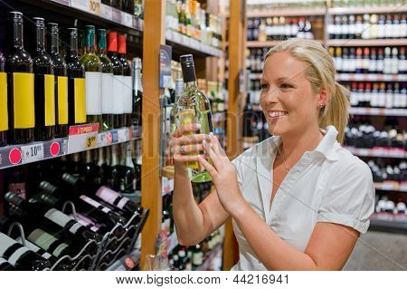 a woman buys wine in a supermarket. wine shelf with wines from around the world.