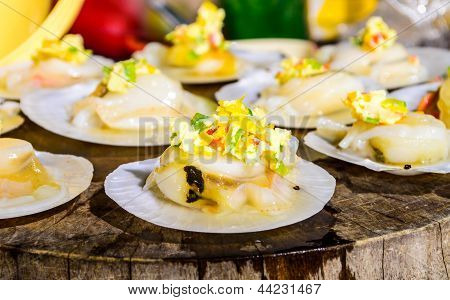 Raw Scallops Topped With Butter, Garlic And Parsley On Chopping Wood.