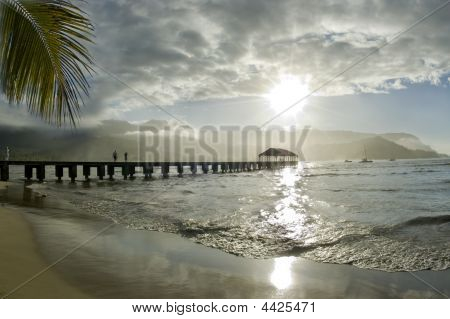 People walking at the pier and watching the beauty of a tropical paradise. Sun reflecting on the sea with the silhouette of the dock surrounded by mountains and one palm tree leaf. Hanalei Bay Kauai. Hawaii Islands. poster