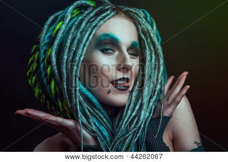Pretty girl with dreadlocks posing in studio poster