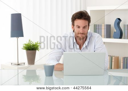 Handsome sitting at living room table, using laptop computer at home, smiling, looking at screen.
