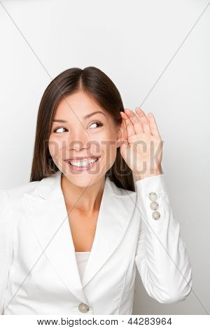 Business woman listening with hand to ear concept. Businesswoman listen to something smiling happy in suit. Beautiful multicultural mixed race Asian Caucasian young female professional in suit.