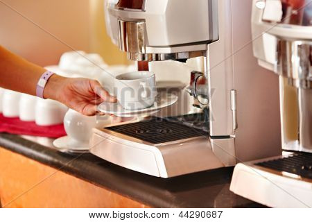 Coffee machine with female hand and cup of coffee.