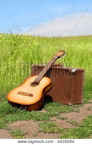 Guitar And Old Leathern Suitcase On The Road
