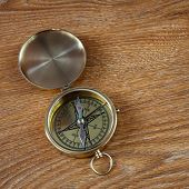 Old compass lying on a wooden board poster