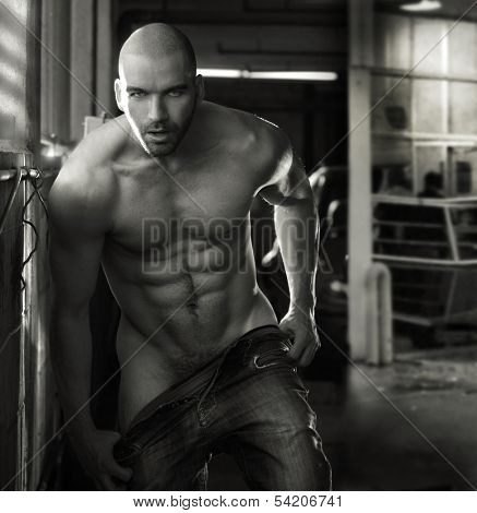 Erotic portrait of a muscular nude man in industrial garage setting