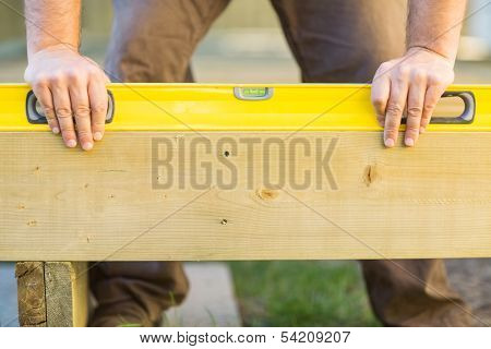 Cropped image of carpenter's hands using spirit level on wood at construction site