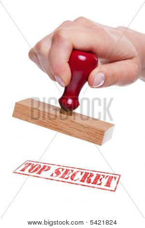 Hand Holding A Rubber Stamp With The Words Top Secret