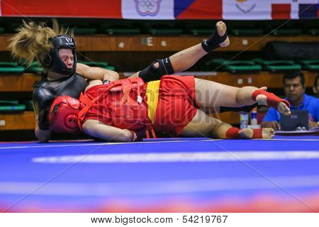 KUALA LUMPUR - NOV 03: China's Mao Yabei (red) fights USA's Ragan Beedy (black) in the Women's 'Sanda' event at the 12th World Wushu Championship on November 03, 2013 in Kuala Lumpur, Malaysia.