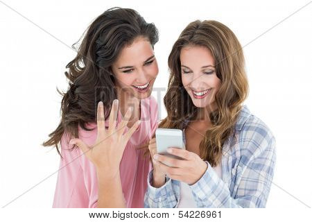 Two cheerful casual young female friends looking at mobile phone against white background