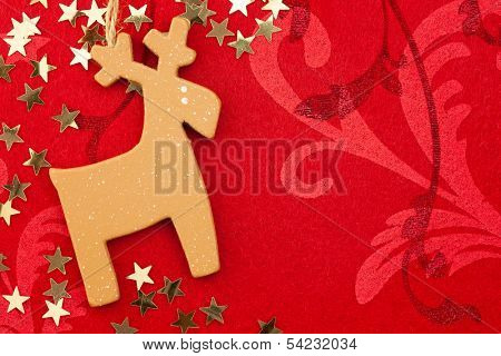 Red Christmas Background with Handmade Reindeer, Golden Stars and Ornament / copy space for your text