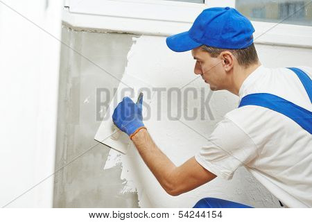 Plasterer at indoor wall renovation decoration with float and plaster
