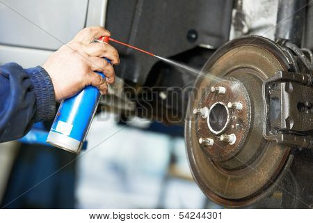 car mechanic cleaning car wheel brake disk from rust corrosion at automobile repair service station