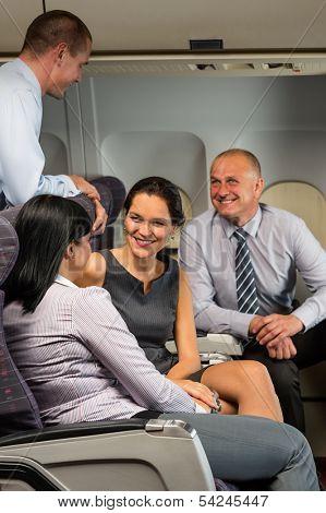 Business people passengers flying airplane talking travel flight cabin